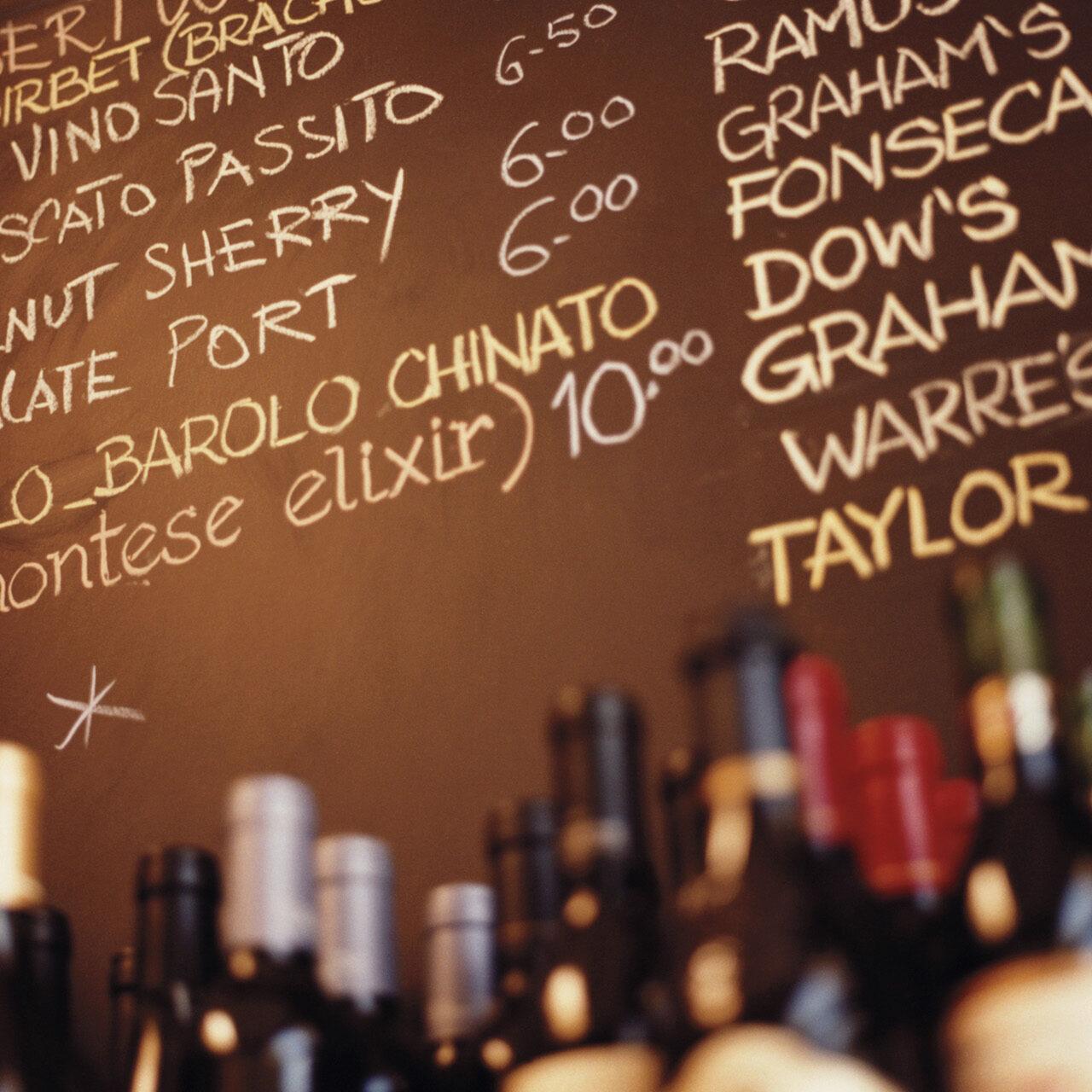 Chalkboard in restaurant with wine menu, wine bottles in foreground